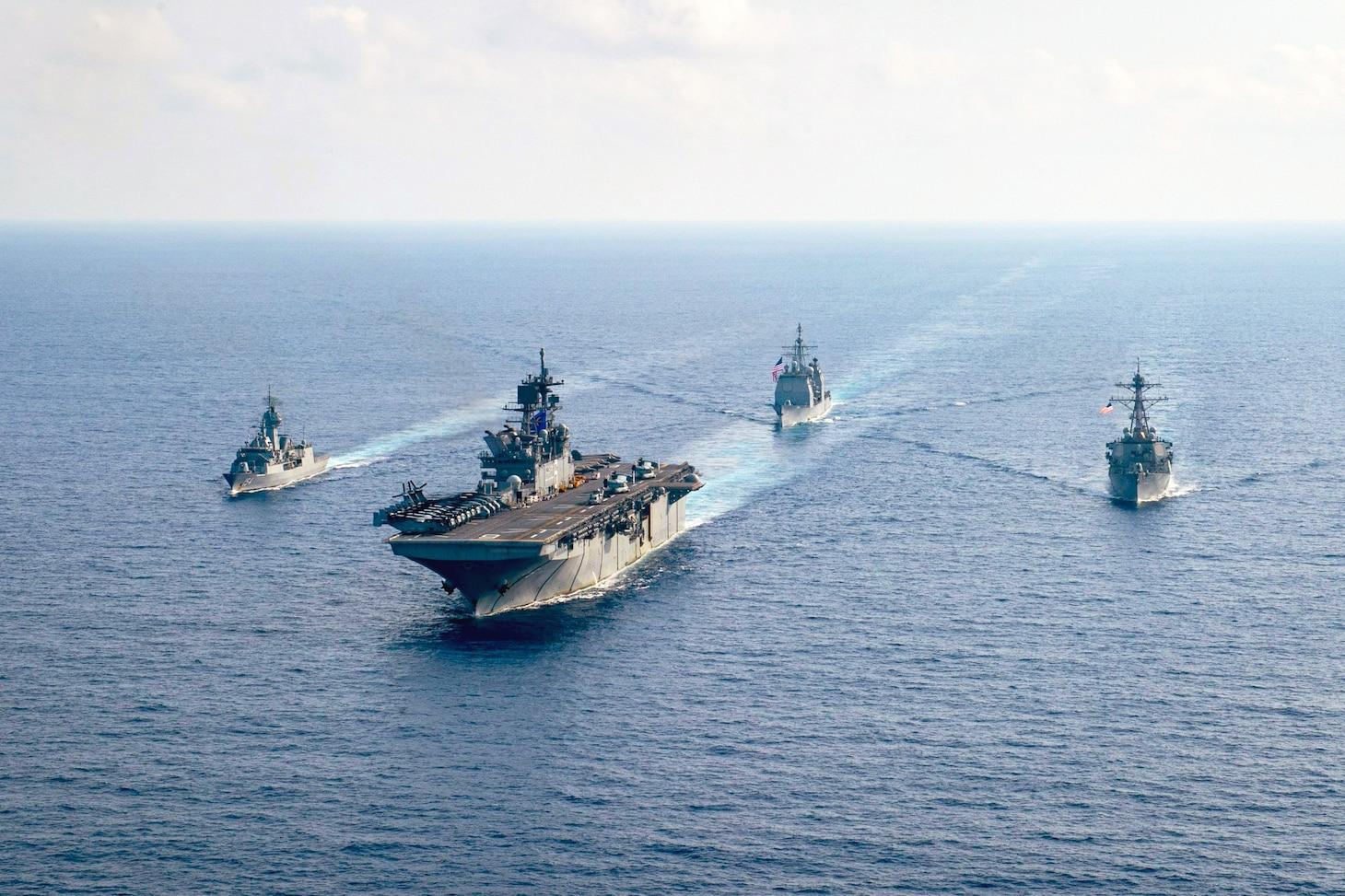 Four ships steam alongside each other on the ocean.