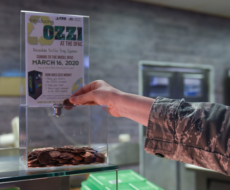 U.S. Air Force Airman 1st Class Leiah Copeland, 52nd Force Support Squadron food service journeyman, demonstrates where to put an OZZI token at Spangdahlem Air Base, Germany, April 20, 2020. OZZI meal trays save Spangdahlem AB $17,000 in funds, promotes recycling to Airmen and families, and helps the environment. (U.S. Air Force photo by Senior Airman Melody W. Howley)