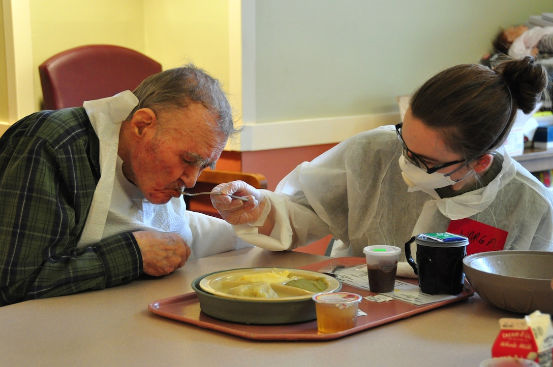 A picture of U.S. Army Pfc. Alexis Varga, a Combat Medic with the 1st Battalion, 114th Infantry Regiment, New Jersey Army National Guard, feeding a resident.