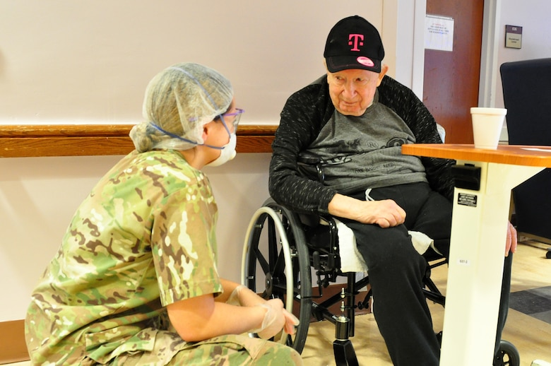 A picture of U.S. Army Spc. Olivia Cordero, a Combat Medic with the 1st Battalion, 114th Infantry Regiment, New Jersey Army National Guard, checking on a resident.