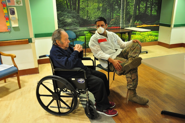 A picture of U.S. Army Spc. Daniel Ortiz, a Combat Medic with the 1st Battalion, 114th Infantry Regiment, New Jersey Army National Guard, spending time with a resident