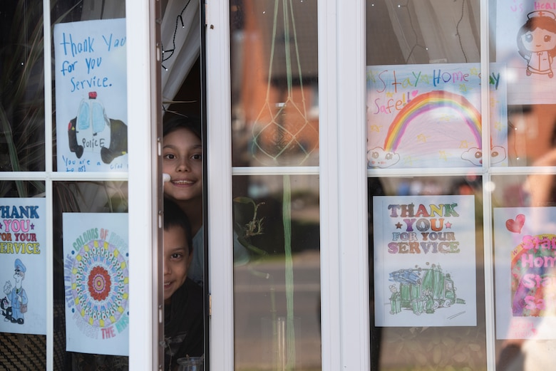 Children of a U.S. Air Force Airman display a rainbow and other artwork in their windows in Liberty Village at Royal Air Force Lakenheath, England, April 22, 2020. The rainbow is a symbol of positivity and is often combined with a message of support for medical professionals serving on the front lines during the current COVID-19 crisis. (U.S. Air Force photo by Airman 1st Class Jessi Monte)