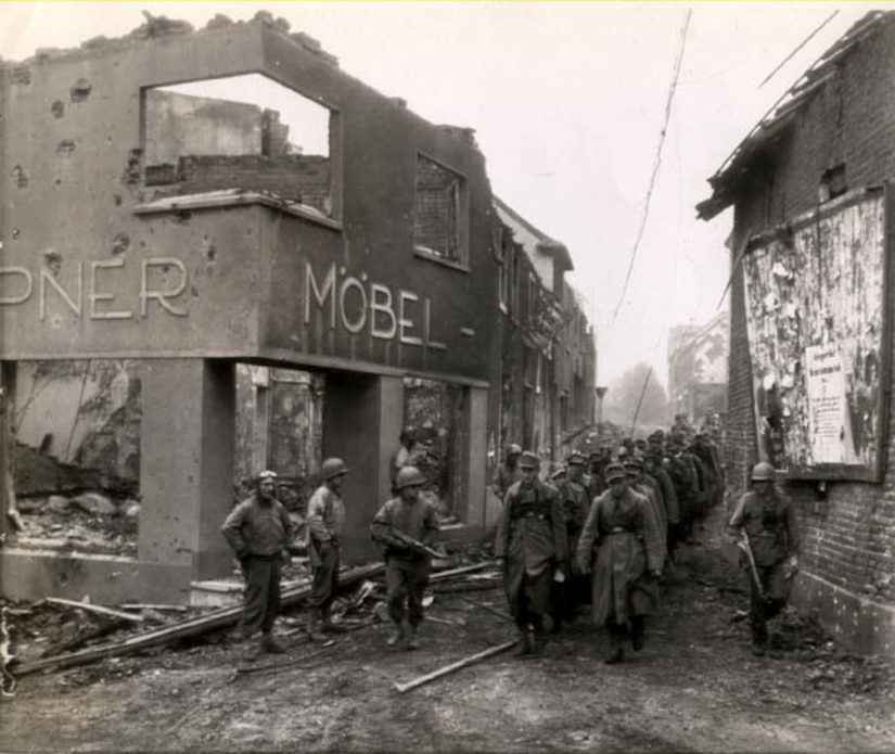 Soldiers guarded by four others march in two lines through a street lined with destroyed buildings.
