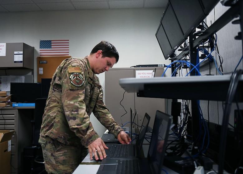 An Airman stands over a desk.