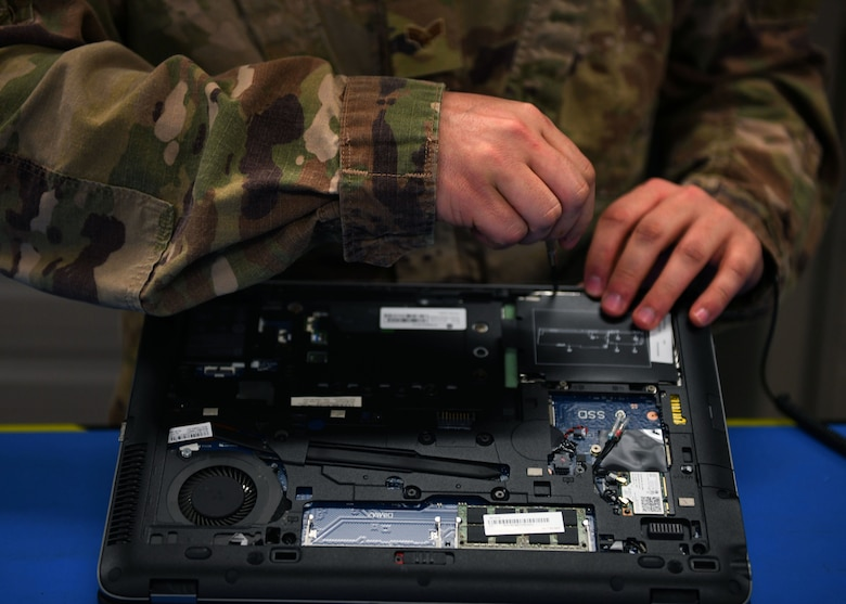 An Airman removes a screw from a laptop.