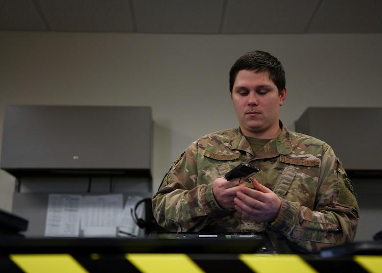 An Airman looks at a computer part.