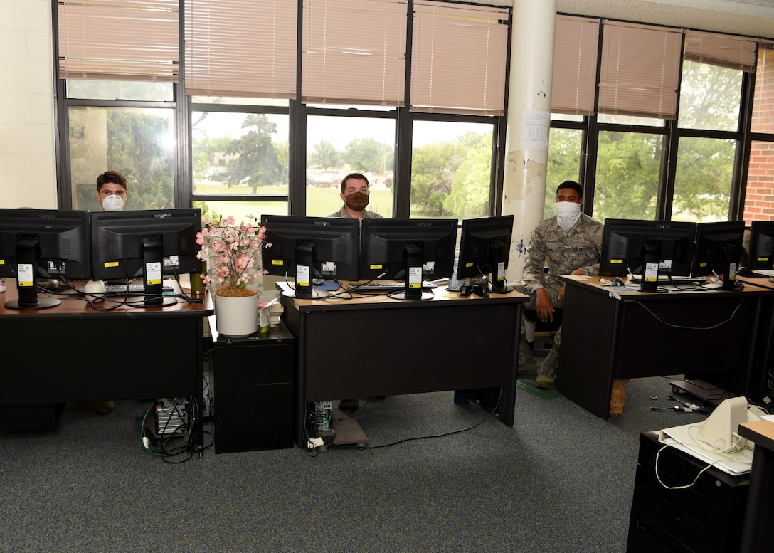 U.S. Air Force client system technicians from the 17 Communications Squadron review work request tickets for computers around base while maintaining a social distance in the COMM building on Goodfellow Air Force Base, Texas, April 22, 2020. The Airmen fixed and solved computer issues on-site and in the field, which instilinged mission readiness while adhering to the Center of Disease Control guidelines during the COVID-19 pandemic. (U.S. Air Force photo by Airman 1st Class Abbey Rieves)