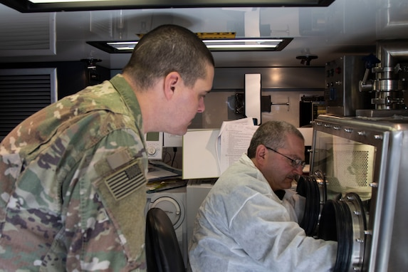 U.S. Army Reserve Maj. Dmitry Pervistky, right, a bio-chemist with the 773rd Civil Support Team, 7th Mission Support Command, from Kaiserslautern, Germany, explains Novel Coronavirus lab procedures to Sgt. Kyle Reitnauer, lab technician with 2nd Armored Brigade Combat Team, 3rd Infantry Division, at Drawsko Pomorskie Training Area, Poland, April 17, 2020. A team of four Soldiers from the 773rd CST is charged with testing incoming personnel to ensure they are not introducing COVID to a relatively COVID-free environment.  (U.S. Army Reserve photo by Staff Sgt. Chris Jackson/Released)
