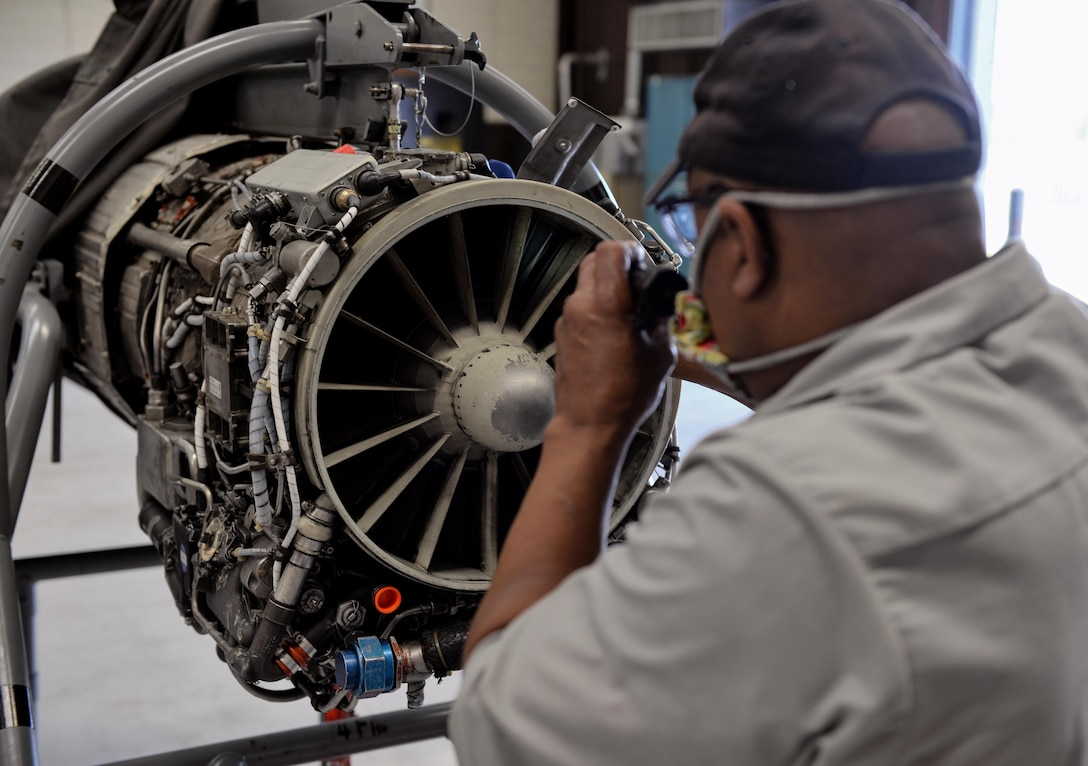 Willy Latham, M1 Support Services propulsion mechanic, inspects a General Electric J85-GE-5 turbojet engine, designed for a T-38 Talon April 17, 2020, at Columbus Air Force Base, Miss. The T-38 is a twin-engine, high-altitude, supersonic jet trainer used in a variety of roles because of its design, economy of operations, ease of maintenance, high performance and exceptional safety record. (U.S. Air Force photo by Airman 1st Class Davis Donaldson)