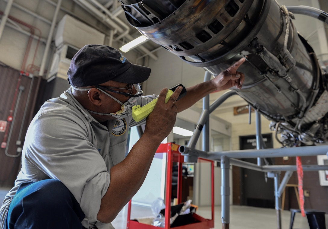 """Willy Latham, M1 Support Services propulsion mechanic, inspects a General Electric J85-GE-5 turbojet engine April 17, 2020, at Columbus Air Force Base, Miss. On an aerospace vehicle, the propulsion system creates thrust by accelerating a gas, or """"working fluid"""". (U.S. Air Force photo by Airman 1st Class Davis Donaldson)"""