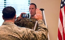 Air National Guard recruiter holds phone displaying video of recruit as an officer administers the oath of enlistment.