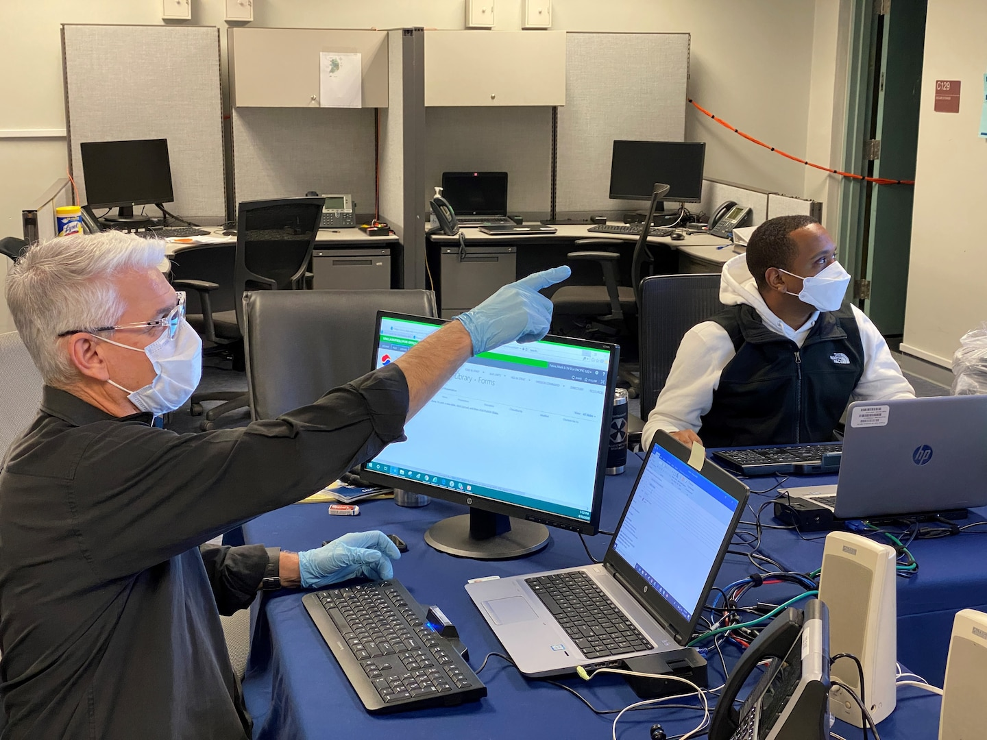 A Korean man sitting at a computer and wearing a mask points to an unidentified object as a black man wearing a mask looks on.