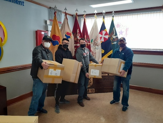 Four men stand in front of flags holding cardboard boxes.