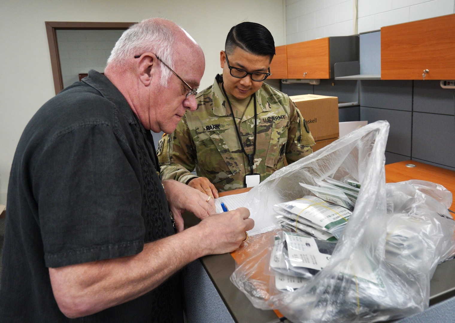 A man signs a piece of paper with a bag of unrecognizable objects next to him as a service member in uniform watches.