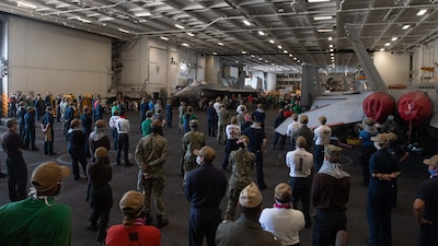 people standing in an aircraft bay listening to speaker