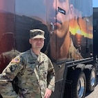 White male in green camouflage uniform in cap stands next to a semi trailer with the picture of a Soldier on it.