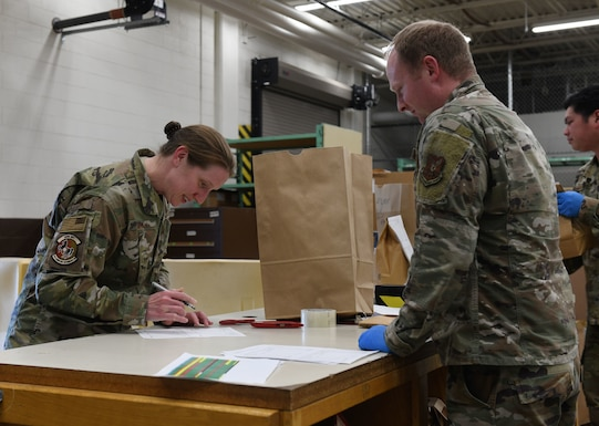 Maj. Saira McGan, the 28th Logistics Readiness operations officer, procures face masks for her squadron at the Flight Service Center on Ellsworth Air Force Base., April 21, 2020. The 28th Contracting Squadron ordered 7,300 face masks for base dissemination, in an effort to battle the COVID-19 pandemic. (U.S. Air Force photo by Airman 1st Class Christina Bennett)