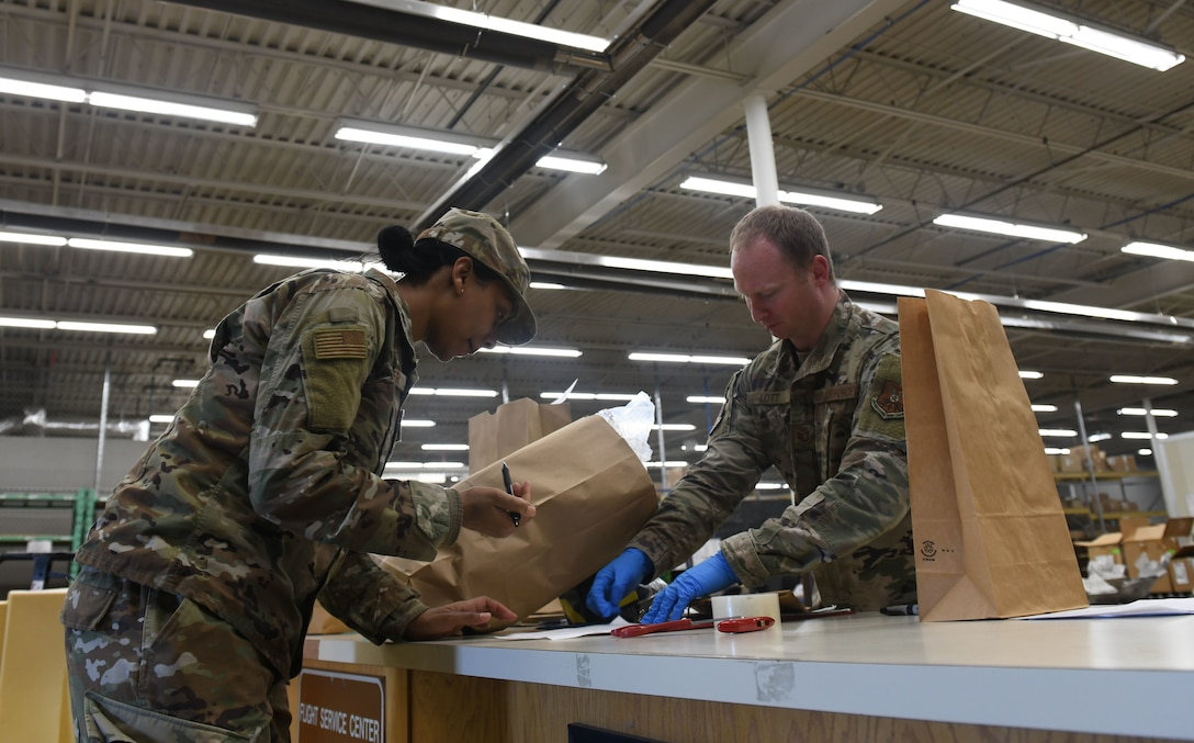 Tech. Sgt. Justin Lott, a 28th Logistics Readiness Squadron asset management section chief, provides a customer with face masks at the Flight Service Center on Ellsworth Air Force Base, S.D., April 21, 2020. The 28th Contracting Squadron ordered 7,300 face masks for base dissemination, in an effort to battle the COVID-19 pandemic. (U.S. Air Force photo by Airman 1st Class Christina Bennett)