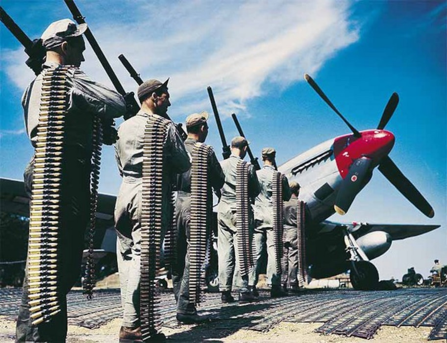 Six crew members lined-up holding ammo next to a P-51 Mustang