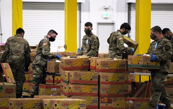 Washington Army National Guard members pack boxes of food at the Food Lifeline temporary site in Seattle April 21, 2020. Members of the Washington Air and Army National Guard are supporting food banks around the state during the COVID-19 pandemic response.