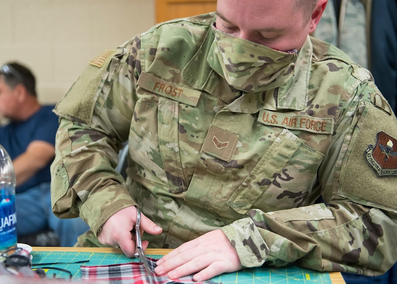 Airman 1st Class Taylor Frost, 56th Equipment Maintenance Squadron aircraft metals technology journeyman, cuts materials for a face mask April, 9, 2020, at Luke Air Force Base, Ariz.