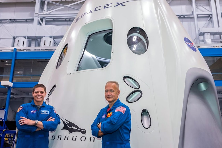 KENNEDY SPACE CENTER, Fla. – NASA astronauts Bob Behnken, Col., U.S. Air Force, left, and Doug Hurley, Col., U.S. Marine Corps, Ret., right, pose in front of SpaceX's Dragon Crew spacecraft. During a brief shared with 50th Wing Staff Agencies Schriever Airmen on April 17, Soichi Noguchi, Japan Aerospace Exploration Agency astronaut, highlighted both astronauts will be part of mission Demo-2, the first manned launch of a spacecraft since the termination of the Space Shuttle Program in 2011, scheduled for May 27, 2020. (SpaceX courtesy photo)