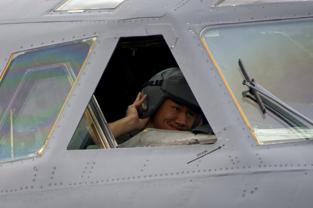 Photo of student pilot putting on helmet.