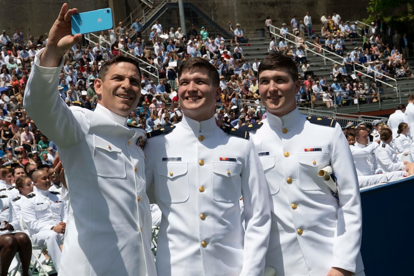 A father and his twin sons, wearing dress white uniforms, smile for a selfie.