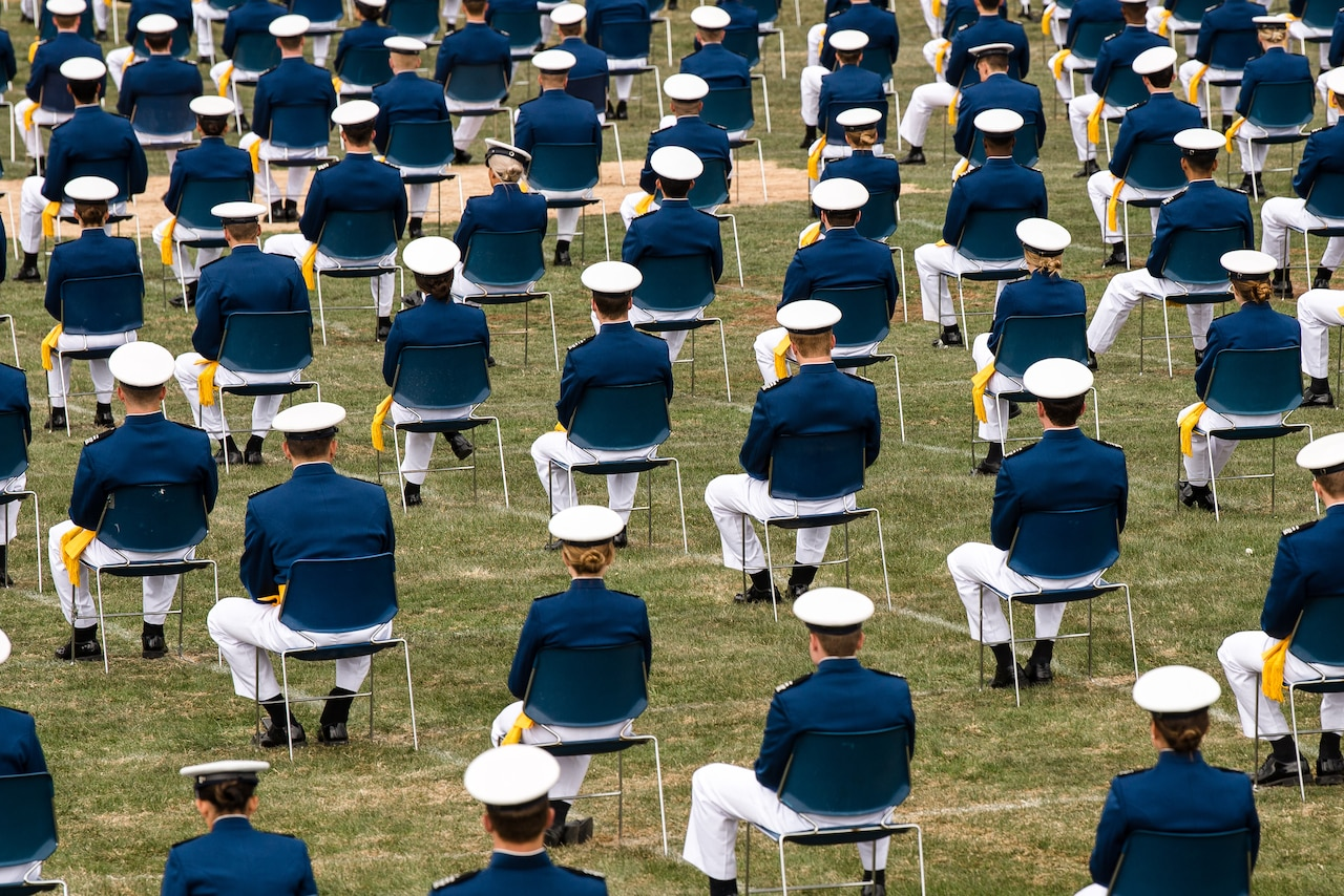 Cadets in dress uniform and cap, sit in lawn chairs spaced 6 feet in each direction.