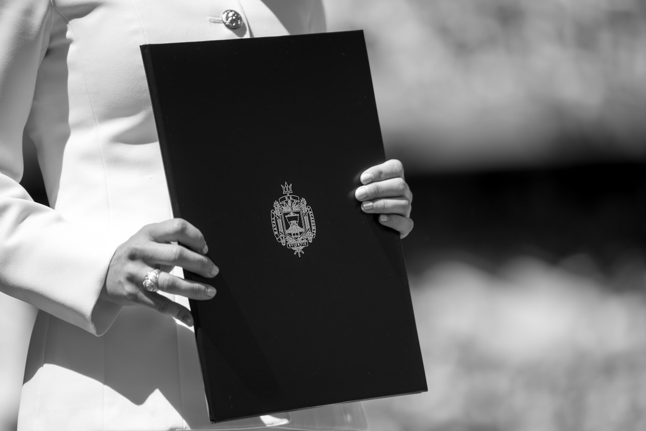 A black-and-white photo of a uniformed midshipman holding a folder with an emblem on it.