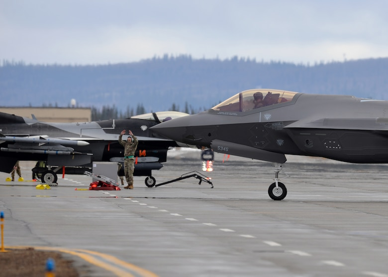 U.S. Air Force Lt. Col. James Christensen, the 356th Fighter Squadron (FS) commander, takes direction from Staff Sgt. Christopher Mashek, a 356th Aircraft Maintenance Unit (AMU) F-35 dedicated crew chief, as he is marsheled in after bringing one of the first two F-35A Lightning II fifth-generation aircraft to Eielson Air Force Base, Alaska, April 21, 2020.