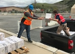 Two men load boxes into a pickup truck