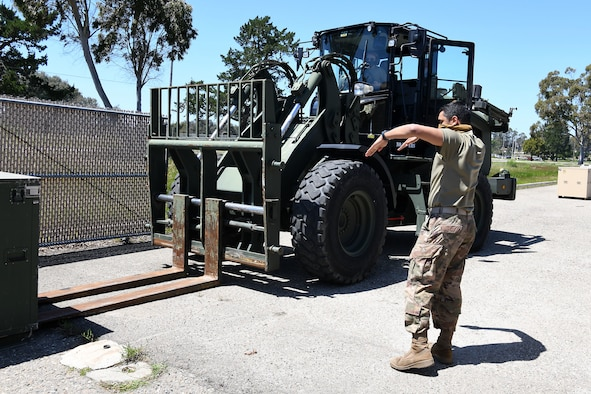 Senior Airman Nicholette Alonge and Airman 1st Class Chance Pickell, 30th Logistics Readiness Squadron ground transportation operators, move containers of cots April 22, 2020, at Vandenberg Air Force Base, Calif.