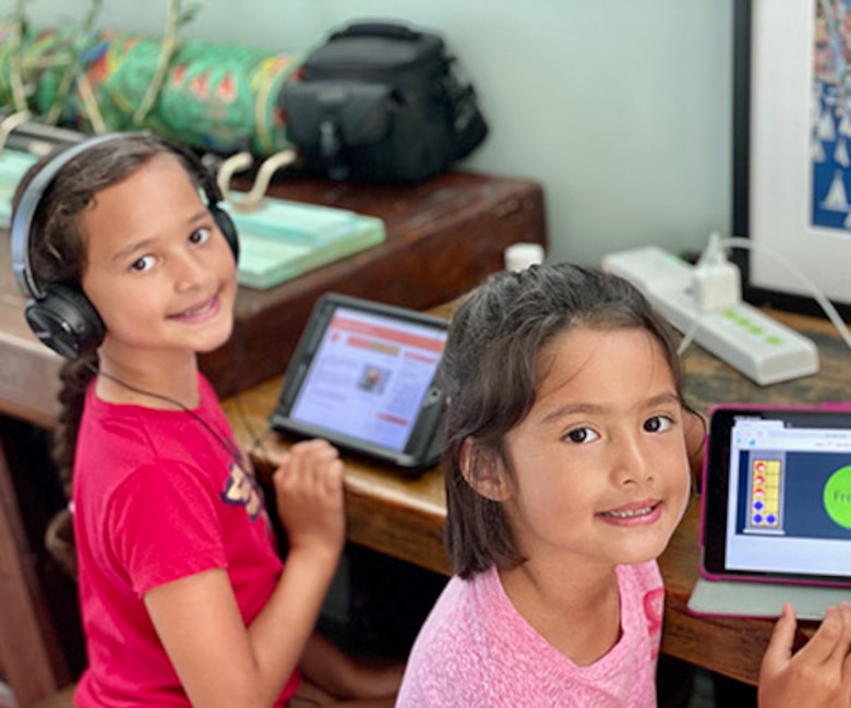 Belen (left) and Paloma (right), daughters of Maj. Sarah Bowles, 325th Logistics Readiness Squadron commander, doing school work from home on tablets. Their school is closed due to the COVID-19 pandemic. (Courtesy Photo)