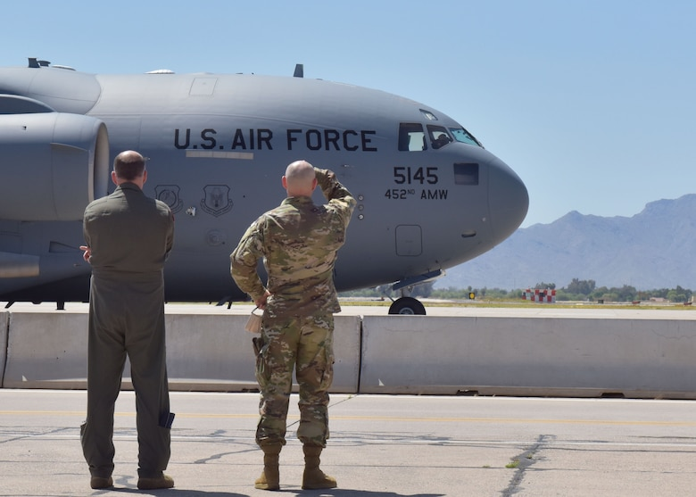 Col. Sean Rassas (left) and Col. James Greenwald (right), 944th Fighter Wing vice-commander and commander, observe the departure of their Reserve Citizen Airmen April 22 at Luke Air Force Base, Ariz. Over a dozen 944th Fighter Wing medics were tasked to aid in Coronavirus response in and around New York City. (U.S. Air Force photo by Tech. Sgt. Louis Vega Jr.)