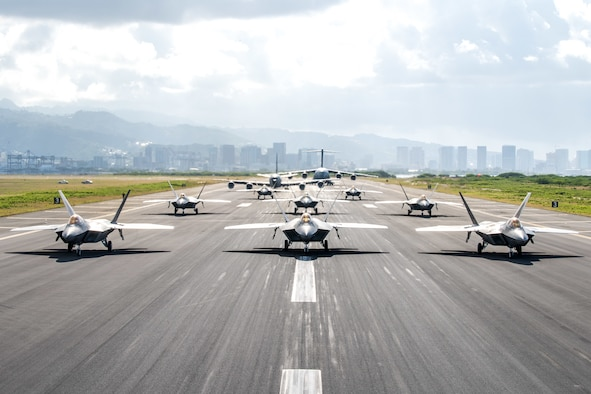 Eight U.S. Air Force F-22 Raptors, a KC-135 Stratotanker and a C-17 Globemaster III taxi on the runway during a routine training schedule April 21, 2020, at Honolulu International Airport, Hawaii. Given the low traffic at the airport due to COVID-19 mitigation efforts, the active-duty 15th Wing and the Hawaii Air National Guard's 154th Wing seized an opportunity to document the operation which showcases readiness and their unique Total Force Integration construct. The units of Team Hickam work together seamlessly to deliver combat airpower, tanker fuel, and humanitarian support and disaster relief across the Indo-Pacific. (U.S. Air National Guard photo by Senior Airman John Linzmeier)