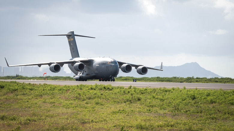 A U.S. Air Force C-17 Globemaster III taxis on the runway during a routine training schedule April 21, 2020, at Honolulu International Airport, Hawaii. Given the low traffic at the airport due to COVID-19 mitigation efforts, the active-duty 15th Wing and the Hawaii Air National Guard's 154th Wing seized an opportunity to document the operation which showcases readiness and their unique Total Force Integration construct. The units of Team Hickam work together seamlessly to deliver combat airpower, tanker fuel, and humanitarian support and disaster relief across the Indo-Pacific. (U.S. Air National Guard photo by Senior Airman John Linzmeier)