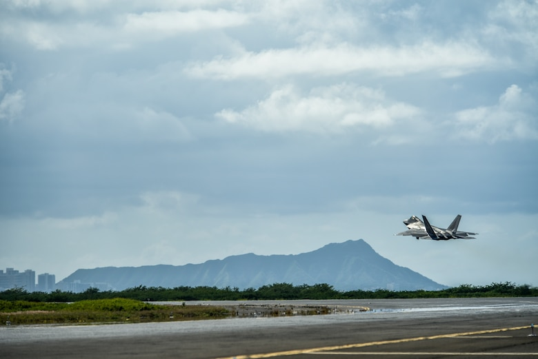 A U.S. Air Force F-22 Raptor takes off from the runway during a routine training schedule April 21, 2020, at Honolulu International Airport, Hawaii. Given the low traffic at the airport due to COVID-19 mitigation efforts, the active-duty 15th Wing and the Hawaii Air National Guard's 154th Wing seized an opportunity to document the operation which showcases readiness and their unique Total Force Integration construct. The units of Team Hickam work together seamlessly to deliver combat airpower, tanker fuel, and humanitarian support and disaster relief across the Indo-Pacific. (U.S. Air Force photo by Tech. Sgt. Anthony Nelson Jr.)