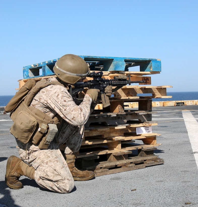 200414-M-MV109-1015 U.S. 5TH FLEET AREA OF OPERATIONS (April 14, 2020) Lance Cpl. Joseph Fischer, field artillery cannoneer, assigned to Fox Battery, Battalion Landing Team 2/8, 26th Marine Expeditionary Unit (MEU), fires an M4 carbine from the kneeling during a live-fire training range aboard the amphibious transport dock USS New York (LPD 21) April 14, 2020. New York, with embarked 26th MEU, is deployed to the U.S. 5th Fleet area of operations in support of naval operations to ensure maritime stability and security in the Central Region, connecting the Mediterranean and Pacific through the Western Indian Ocean and three strategic choke points. (Marine Corps photo by Staff Sgt. Patricia A. Morris)