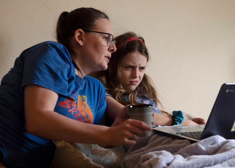 Beth and Bailey, wife and daughter of U.S. Army Sgt. 1st Class Cody Camp, U.S. Army Recruiting Command senior guidance counselor, read over a classwork assignment at their home in Kaiserslautern, Germany, April 14, 2020.