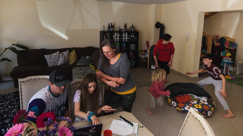 U.S. Army Sgt. 1st Class Cody Camp, left, U.S. Army Recruiting Command senior guidance counselor and his wife, Beth, center, assist their daughter with her classwork and as their other children play at their home in Kaiserslautern, Germany