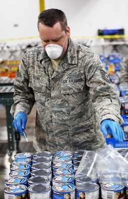 A member of the Washington Air National Guard opens a crate of canned food at the Food Lifeline temporary site in Seattle, Wash. on April 21, 2020. Members of the Washington Air and Army National Guard are supporting food banks around the state during the COVID-19 pandemic response. (U.S. National Guard photo by Joseph Siemandel)