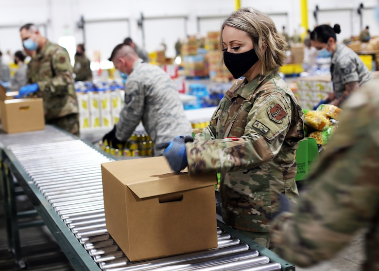 A member of the Washington Air National Guard closes an emergency food box packed at the Food Lifeline temporary site in Seattle, Wash. on April 21, 2020. Members of the Washington Air and Army National Guard are supporting food banks around the state during the COVID-19 pandemic response. (U.S. National Guard photo by Joseph Siemandel)