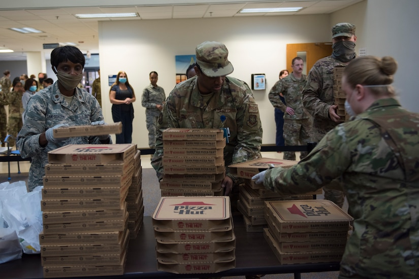 Major Michelle Law-Gordon, 628th Air Base Wing senior installation chaplain, and Master Sgt. Jennifer Deprinzio, 628th Air Base Wing superintendent of religious affairs, prepare to pass out food at the 628th Medical Group at Joint Base Charleston, S.C. April 22, 2020. JB Charleston chaplains passed out pizza and sandwiches to raise morale and thank Medical Group personnel for all their hard work during the COVID-19 pandemic. The chaplains wore masks and gloves to protect the Airmen they handed food to.