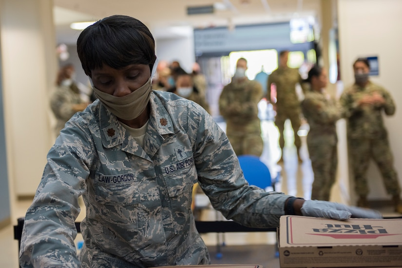 Major Michelle Law-Gordon, 628th Air Base Wing senior installation chaplain, prepares to pass out food at the 628th Medical Group at Joint Base Charleston, S.C. April 22, 2020. JB Charleston chaplains passed out pizza and sandwiches to raise morale and thank Medical Group personnel for all their hard work during the COVID-19 pandemic. The chaplains wore masks and gloves to protect the Airmen they handed food to.