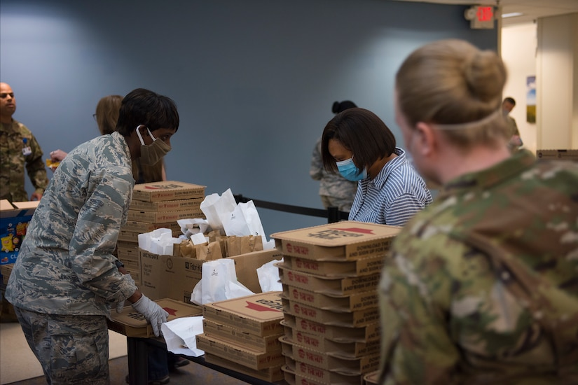 Major Michelle Law-Gordon, 628th Air Base Wing senior installation chaplain, and Master Sgt. Jennifer Deprinzio, 628th Air Base Wings superintendent of religious affairs, pass out food at the 628th Medical Group at Joint Base Charleston, S.C. April 22, 2020. JB Charleston chaplains passed out pizza and sandwiches to raise morale and thank Medical Group personnel for all their hard work during the COVID-19 pandemic. The chaplains wore masks and gloves to protect the Airmen they handed food to.