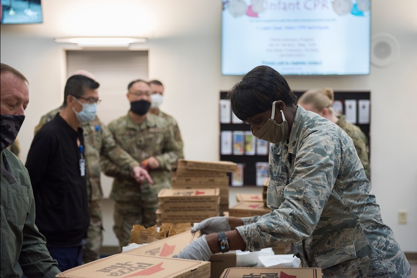 Major Michelle Law-Gordon, 628th Air Base Wing senior installation chaplain, passes out food at the 628th Medical Group at Joint Base Charleston, S.C. April 22, 2020. JB Charleston chaplains passed out pizza and sandwiches to raise morale and thank Medical Group personnel for all their hard work during the COVID-19 pandemic. The chaplains wore masks and gloves to protect the Airmen they handed food to.