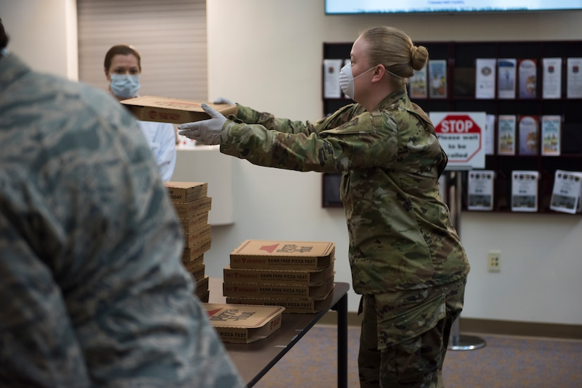 Master Sgt. Jennifer Deprinzio, 628th Air Base Wing superintendent of religious affairs, passes out food at the 628th Medical Group at Joint Base Charleston, S.C. April 22, 2020. JB Charleston chaplains passed out pizza and sandwiches to raise morale and thank Medical Group personnel for all their hard work during the COVID-19 pandemic. The chaplains wore masks and gloves to protect the Airmen they handed food to.
