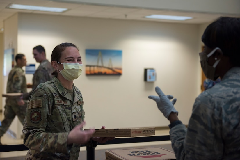 Major Michelle Law-Gordon, 628th Air Base Wing senior installation chaplain, and Lt. Col. Christine Smetana, the 628th Operational Medical Readiness Squadron Commander, talk about the morale event happening at the 628th Medical Group at Joint Base Charleston, S.C. April 22, 2020. JB Charleston chaplains passed out pizza and sandwiches to raise morale and thank Medical Group personnel for all their hard work during the COVID-19 pandemic. The chaplains wore masks and gloves to protect the Airmen they handed food to.