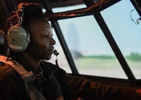 A woman siting in the pilot seat of a C-130 simulator.